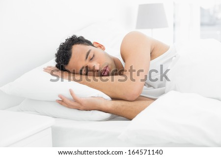 Side view of a young man sleeping in bed at home - stock photo