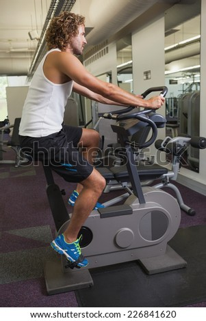 Side view of a young man working out on exercise bike at the gym