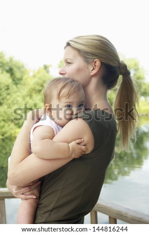 Side view of a young mother carrying daughter against the lake - stock photo
