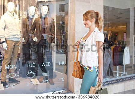 Side view of a young smiling tourist woman walking by fashion store window carrying shopping bags, city outdoors. Smart consumer girl in shop exterior with glass reflections, lifestyle. - stock photo