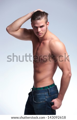 side view of a young topless man standing with his hand in his hair and the other in his back pocket while looking into the camera. on gray background - stock photo