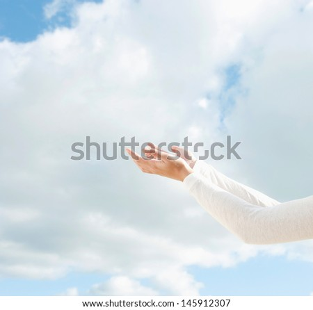 Side view of a young woman arms raised up to the sky holding her empty hands together against a blue sky with clouds during a sunny day outdoors.