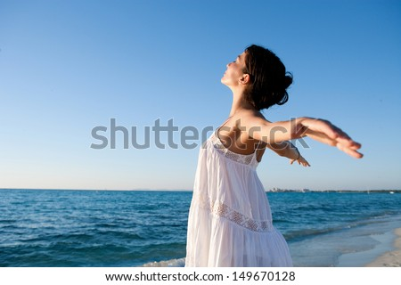 Side view of a young woman breathing fresh air while standing on a beach shore with her arms outstretched back, enjoying the intense blue sea and sky at sunset during a vacation.