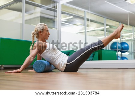 Side view of a young woman doing fitness exercise in the gym - stock photo