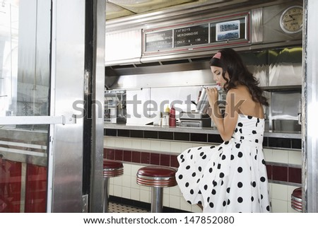 Side view of a young woman drinking shake at the diner counter