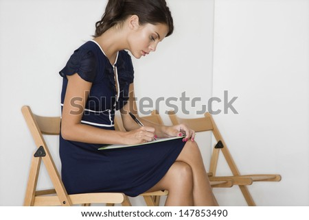 Side view of a young woman in blue dress writing at waiting room