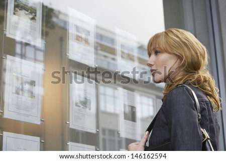 Side view of a young woman looking at window display at real estate office - stock photo