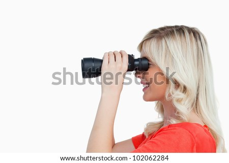 Side view of a young woman looking through binoculars against a white background - stock photo