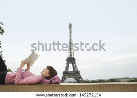 Side view of a young woman lying on balcony and reading book in front of Eiffel Tower - stock photo