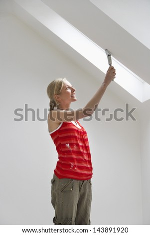 Side view of a young woman painting the ceiling slope - stock photo