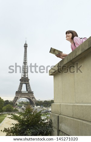 Side view of a young woman reading book on balcony against Eiffel Tower - stock photo
