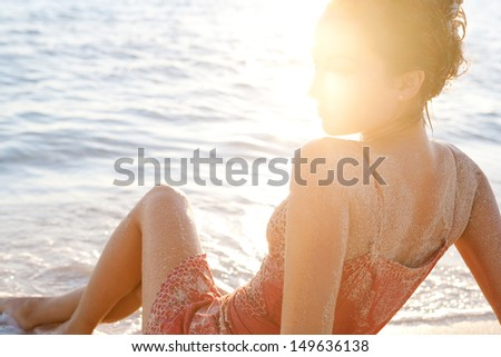 Side view of a young woman sitting down on the shore of a sandy beach, bathing her feet in the sea waves while dressed at sunset during a hot summer vacation, with flare on her face.