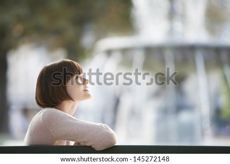 Side view of a young woman sitting on bench in front of blurred fountain - stock photo