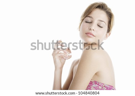 Side view of a young woman spraying perfume on her bare shoulders, smiling. - stock photo