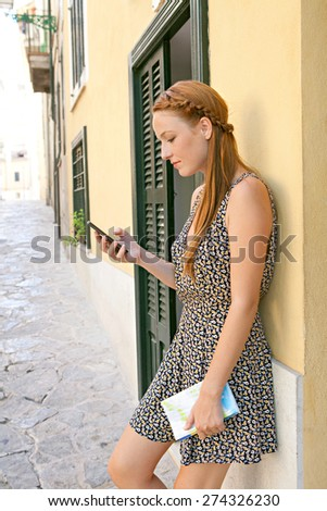Side view of a young woman visiting a picturesque stone pavement street, using a smartphone mobile to network, holding a map in a destination city on summer holiday, outdoors. Travel technology. - stock photo