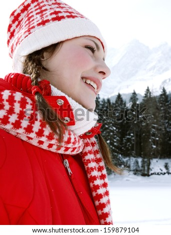 Side view of a young woman walking in the snow forest mountains landscape, contemplating the scenery and relaxing during a sunny day on a skiing winter holiday.