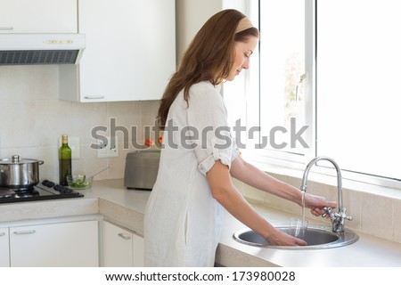 Side view of a young woman washing glass at washbasin in the kitchen at home - stock photo