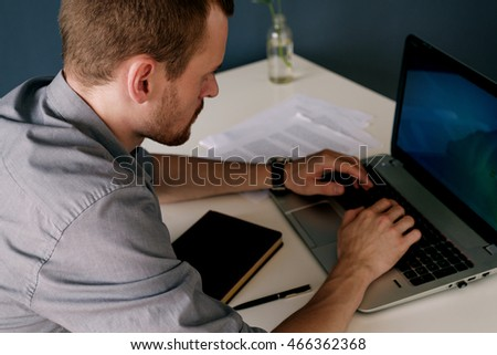 Side view of adult businessman working on laptop in office