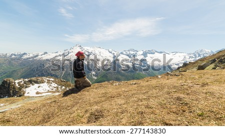 Side view of adult hiker with sunglasses and beard kneeling on the mountain summit. Panoramic view on the snowcapped alpine arc in the background. Natural warm tones, Piedmont, Italy. - stock photo
