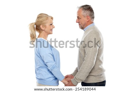 Side view of affectionate mature couple standing together holding hands and looking at each others eyes against  white background