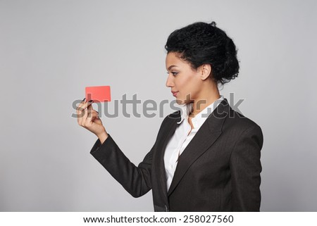 Side view of african american business woman showing blank credit card, over gray background - stock photo