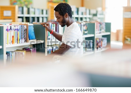 Side view of African American male librarian arranging books in bookstore