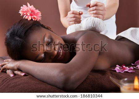 Side view of African American woman enjoying herbal massage at spa salon - stock photo