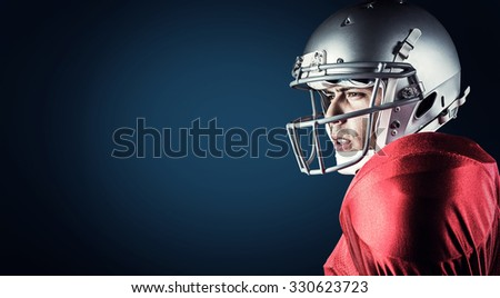 Side view of American football player looking away against blue background with vignette