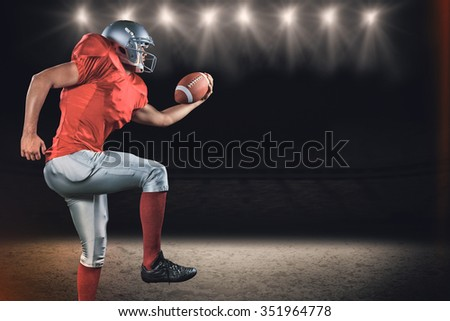 Side view of American football player running while holding ball against desert landscape