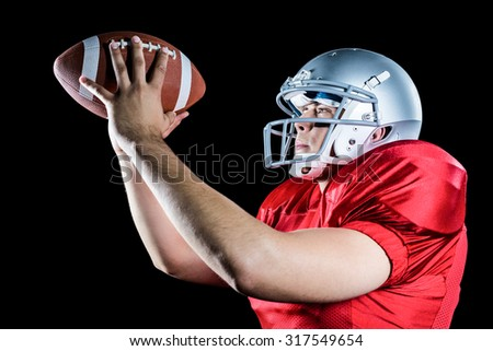Side view of American football player throwing ball against black background - stock photo