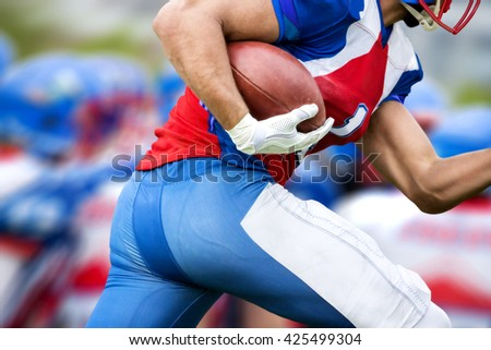 Side view of american football player who runs with the ball to make a touchdown. In the blurred background there can be seen his run protecting team. - stock photo