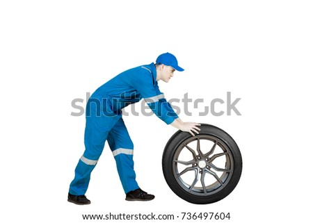 Side view of American male mechanic pushing a car wheel in the studio, isolated on white background