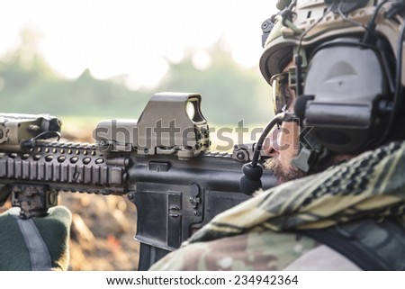 Side view of American Soldier aiming a rifle - stock photo