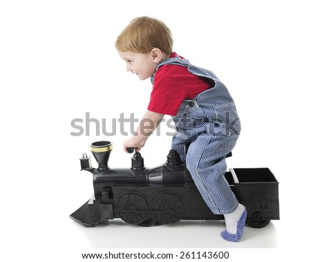 Side view of an adorable 2-year-old train engineer scooting along on a toy train engine.  On a white background. - stock photo