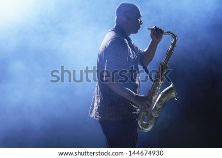Side view of an African American man playing saxophone against smoky background - stock photo