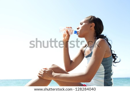 "Side view of an ""african american"" woman sitting by the sea drinking mineral water and taking a break from doing sport, against a blue sky and sea. - stock photo"