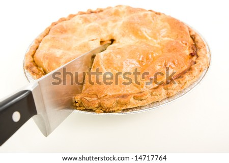 Side view of an apple pie being cut.
