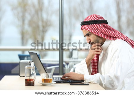 Side view of an arab saudi man worried working with a laptop in a coffee shop interior with the terrace in the background - stock photo