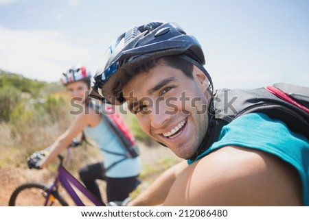 Side view of an athletic couple mountain biking - stock photo