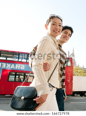 Side view of an attractive and joyful Japanese tourist couple walking passed a double decker red bus in the city of London while on vacation during a sunny day, outdoors. - stock photo