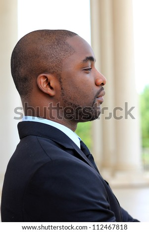 Side View of an Attractive, Young Professional Mature African American Businessman Looking Forward While Thinking and Wearing a Black Suit amd Tie - stock photo