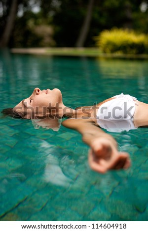 Side view of an attractive young woman floating on a swimming pool, smiling. - stock photo