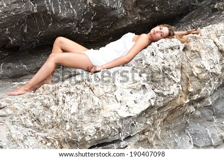 Side view of an attractive young woman laying on a coastal dark and textured rock mountain wrapped in a white sarong, sunbathing and relaxing during a summer holiday. Beauty and health lifestyle. - stock photo