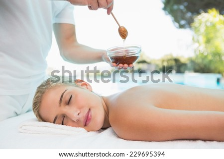 Side view of an attractive young woman receiving spa treatment with honey - stock photo