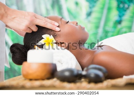 Side view of an attractive young woman receiving temple massage at spa center - stock photo