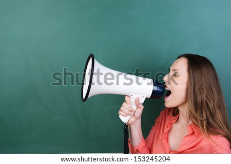 Side view of an attractive young woman standing in front of a blank green blackboard with copyspace yelling into a megaphone - stock photo
