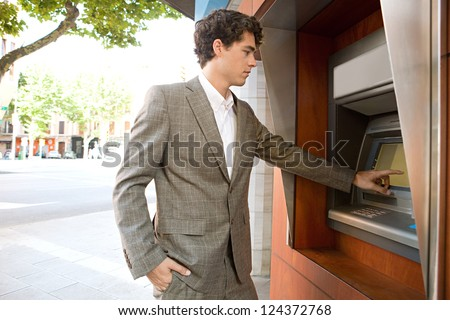 Side view of an elegant businessman withdrawing money from a wood decorated bank cash point in the city, outdoors.