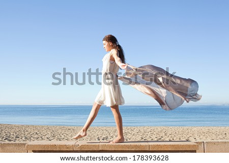 Side view of an elegant woman rising a floating sarong up with her arms against a bright blue sky and sea on a holiday beach, taking a step on a stone wall, outdoors. Beauty and lifestyle. - stock photo