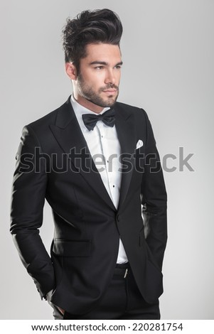 Side view of an elegant young man in tuxedo looking away from the camera while holding his hand in pocket. - stock photo