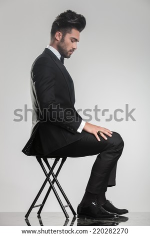 Side view of an elegant young man sitting on a stool looking down. On grey studio brackground. - stock photo